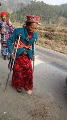 A woman from Haku 8 who lives in Sankhule IDP camp. She broke her leg during the earthquake. We offered her a ride to her camp.