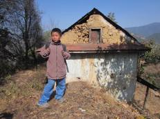 Raju Syngtan, age 9 (Class 2), in front of his ruined house.