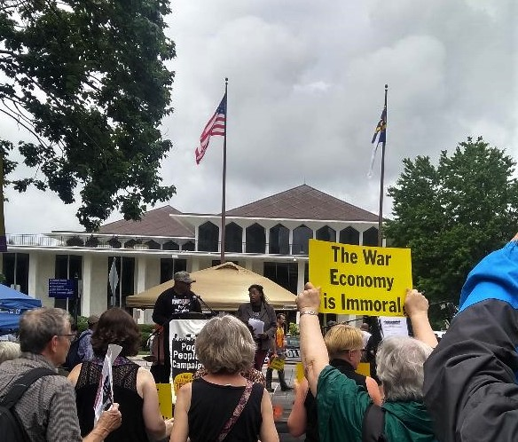 "Group of people listening to speaker at rally outside with one person holding up yellow sign with black writing that says ""The War Economy is Immoral"""