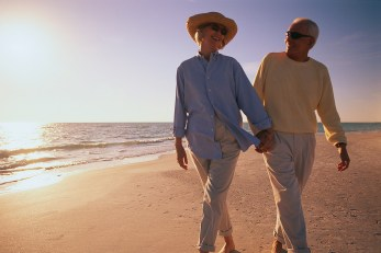 Older Couple Walking Along Beach
