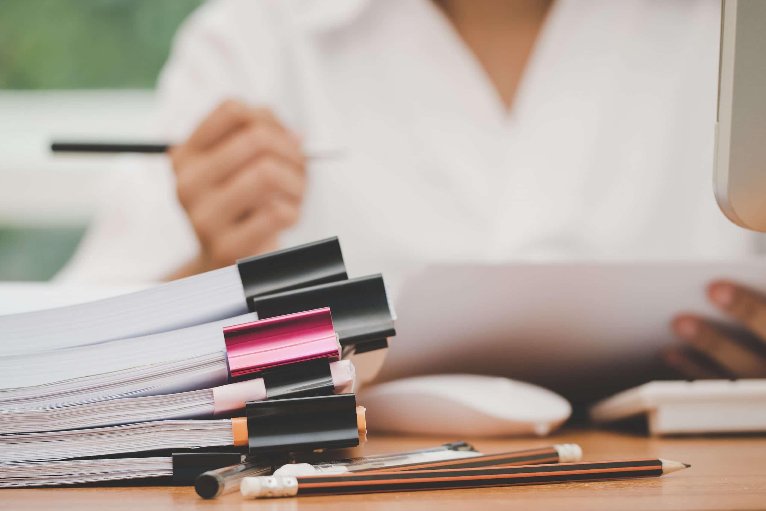 Femme a son bureau écrivant sur un document avec des dossiers devant elle