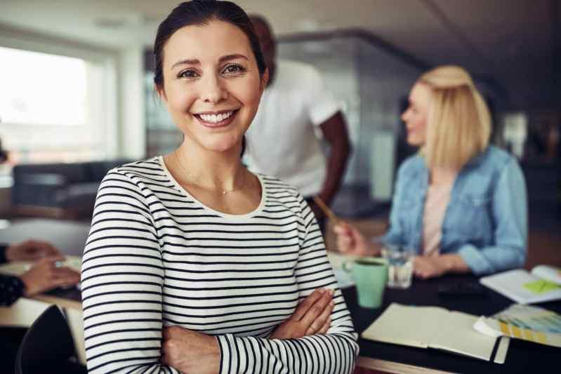 Jeune femme d'affaires souriante et assise les bras croisés à une table de bureau avec des collègues parlant ensemble en arrière-plan
