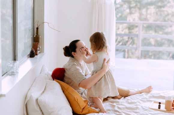 mother and daughter having fun in bedroom while spending time together at home