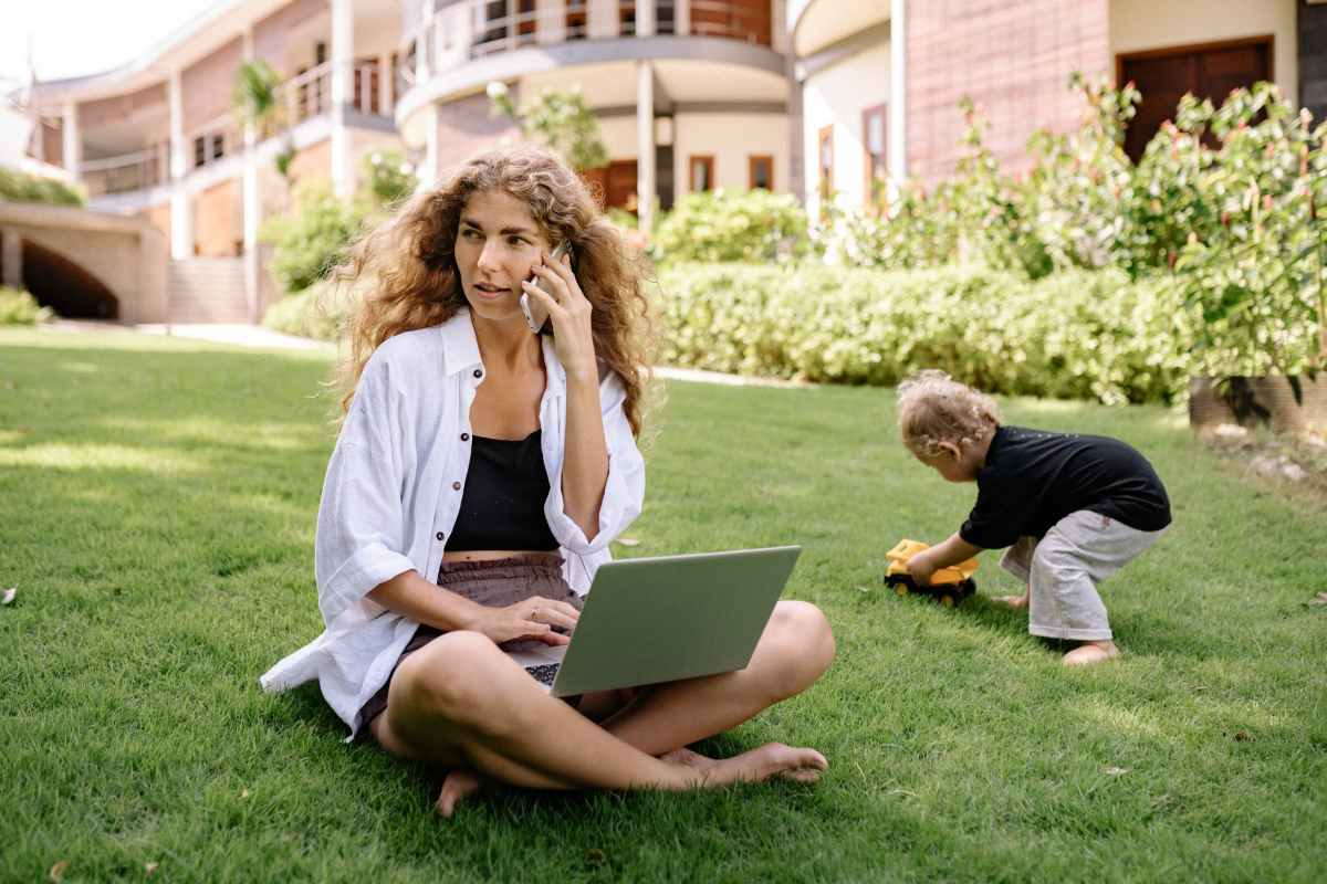 photo of woman using silver laptop with her child playing on grass field