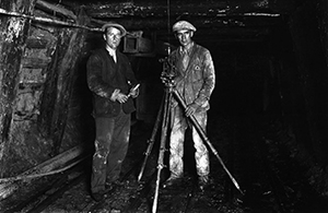 Photographer and miner Joseph Divis and mine manager Tas Hogg surveying the old Blackwater mine with assistant Nick Brett (left). Behind Nick's shoulder is the ventilation shaft. (Pic: Ministry for Culture and Heritage.)