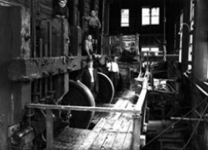 The largest room in the battery building held the stampers, seen here at the top end, where camshafts lifted and dropped the heavy stamp rods. In the foreground is battery manager Jack McEwin, with sons Andrew and Ian behind, and aptly named assistant battery manager, Frank Orr, at right. All of this and the associated machinery was powered by water.