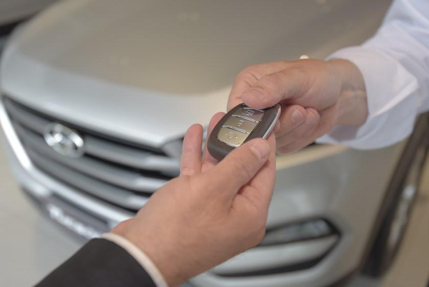 Salesperson delivers car keys to customer