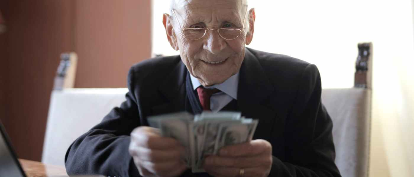 happy senior businessman counting money while sitting at table with laptop