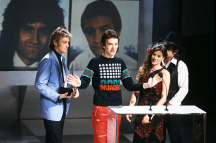 roger-taylor-and-john-deacon-receiving-the-award-for-favourite-pop-single-for-another-one-bites-the-dust-from-barbi-benton-and-johnny-paycheck-american-music-awards-january-1981-1