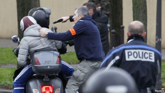 Policías frances arrestan a dos jóvenes en una motocicleta cuando se acercaban a la zona donde un atacante ha tomado rehenes en un supermercado judío en el este de París.