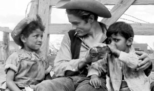 Actor James Dean with Mexican children during the filming of Giant.