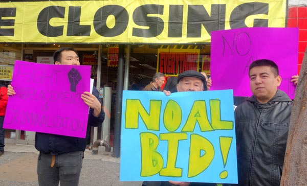 El comerciante Rubén Peña con un letrero de No al BID, y Percy Luján a la derecha.