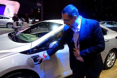 Javier Guzmán de la General Motors señalando la conexión del sistema de carga eléctrica de uno de los autos de la Chevrolet.