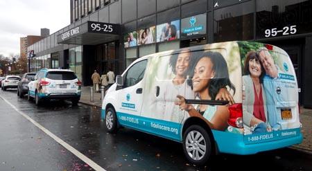Dos furgonetas de Fidelis Care frente a las nuevas oficinas en Queens Boulevard.