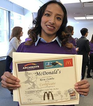 Zumba Rosa, empleada de McDonald's exhibiendo su cartón de graduación de ESL.