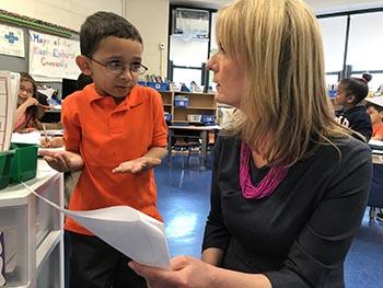 Mathew Beckam, de 5 años, explicándole a la directora Stabora lo que escribió en inglés.