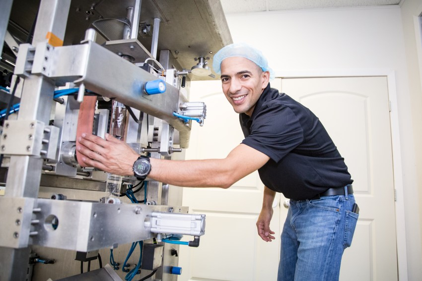 Owner of a small business stands by his candy manufacturing machine.