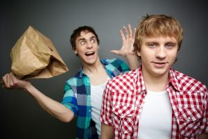 Crazy guy ready to explode paper bag behind his friend's back - wow that's SO crazy. Ha!