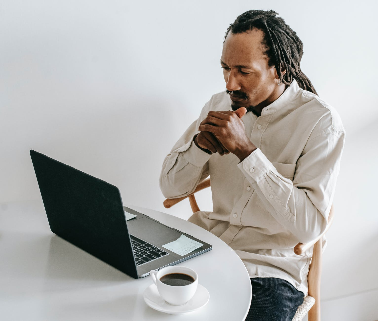 serious black man working on laptop in light room