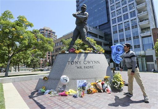 """A mourner looks up at the Tony Gwynn """"Mr. Padre"""" statue outside Petco Park Monday, June 16, 2014, in San Diego. Gwynn, an eight time National League batting champion and a member of Baseball Hall of Fame, died Monday from cancer. (AP Photo/Lenny Ignelzi)"""