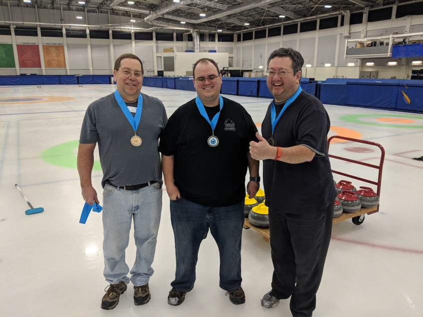"The members of Team 20/20 — from the left, Joe, Andrew and Ryan — pose after receiving medals for winning the ""B"" bracket during the winter 2018 Monday curling league at the Utah Olympic Oval."