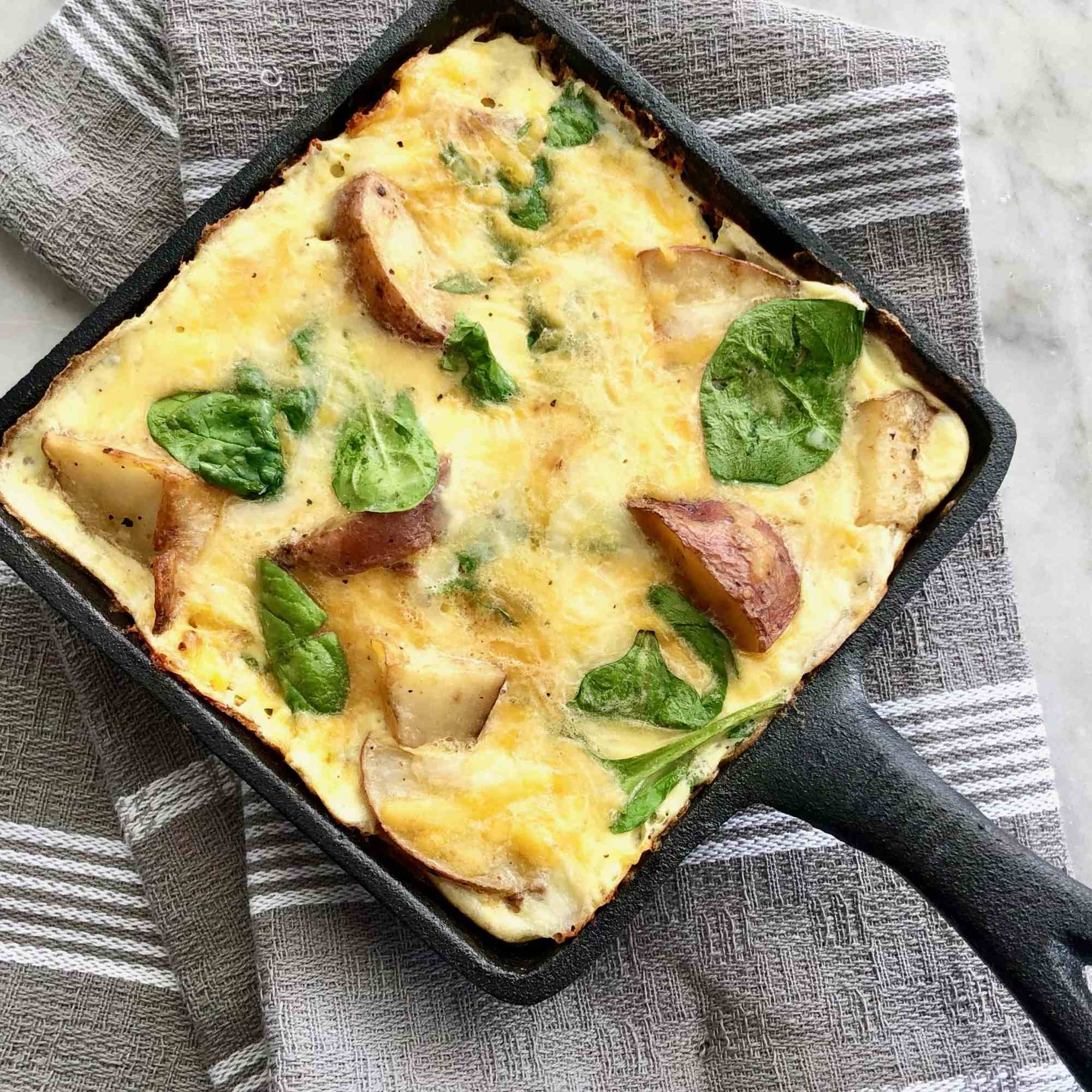 quiche with potatoes and spinach in a cast iron skillet.