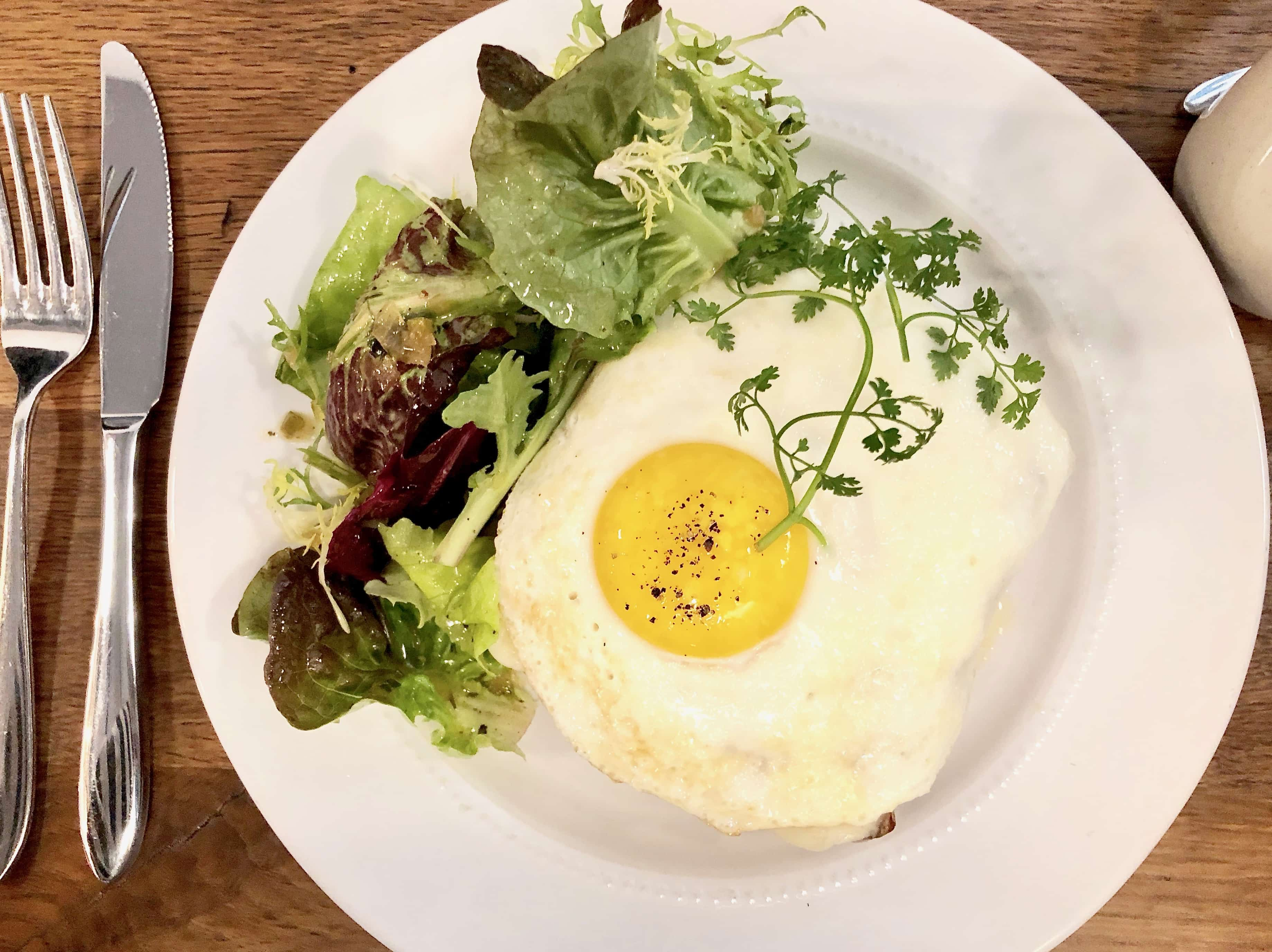 fried eggs with mixed greens on a white plate