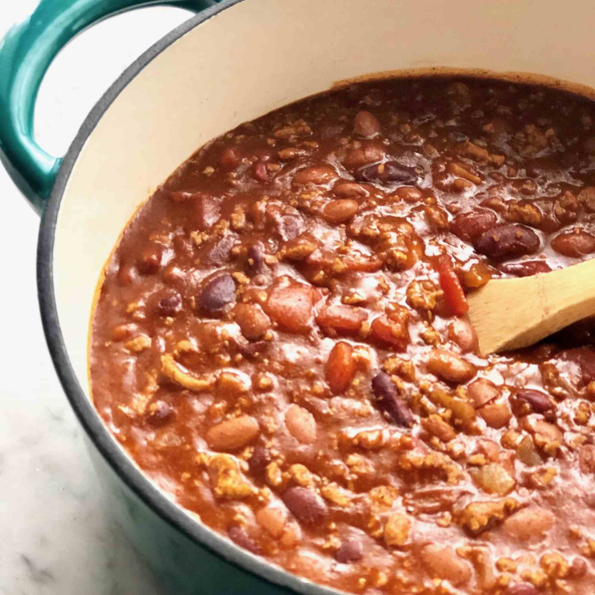 campfire chili in a dutch oven with a wooden spoon
