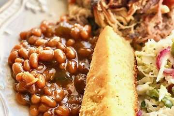 barbecue and baked beans on a white plate