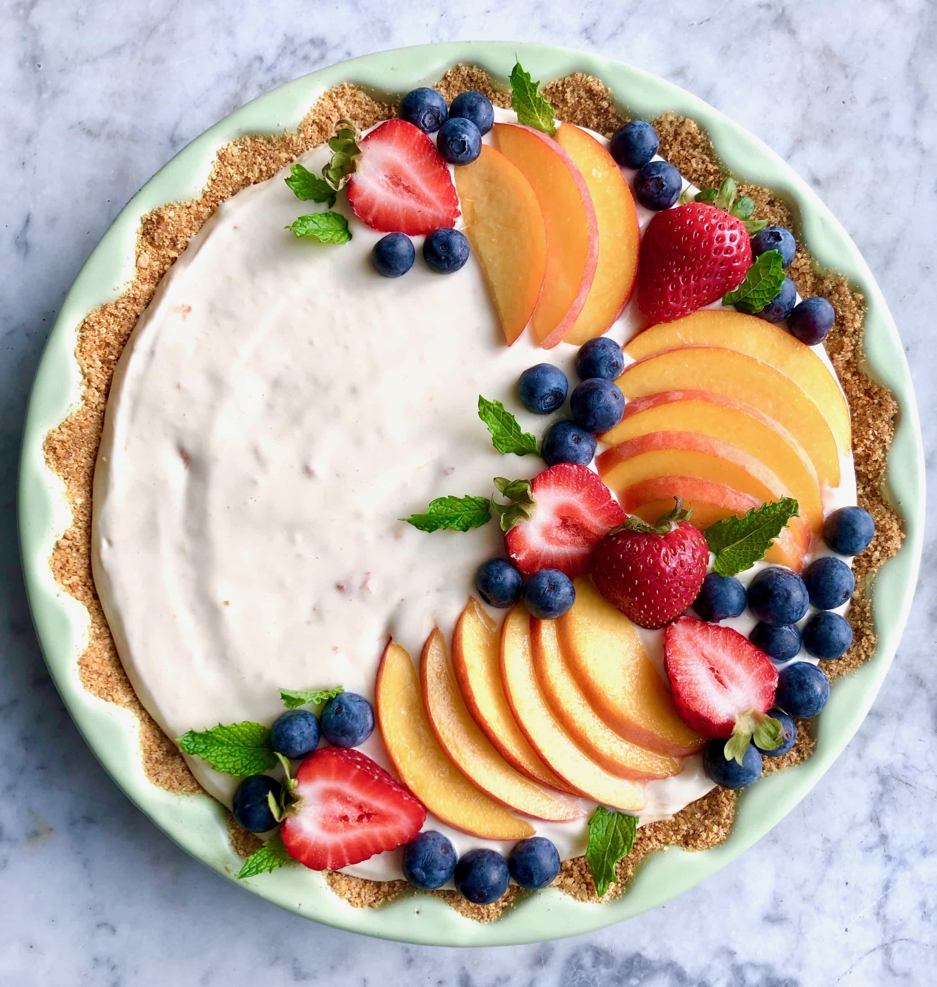 peach tart with graham cracker crust in a green tart dish