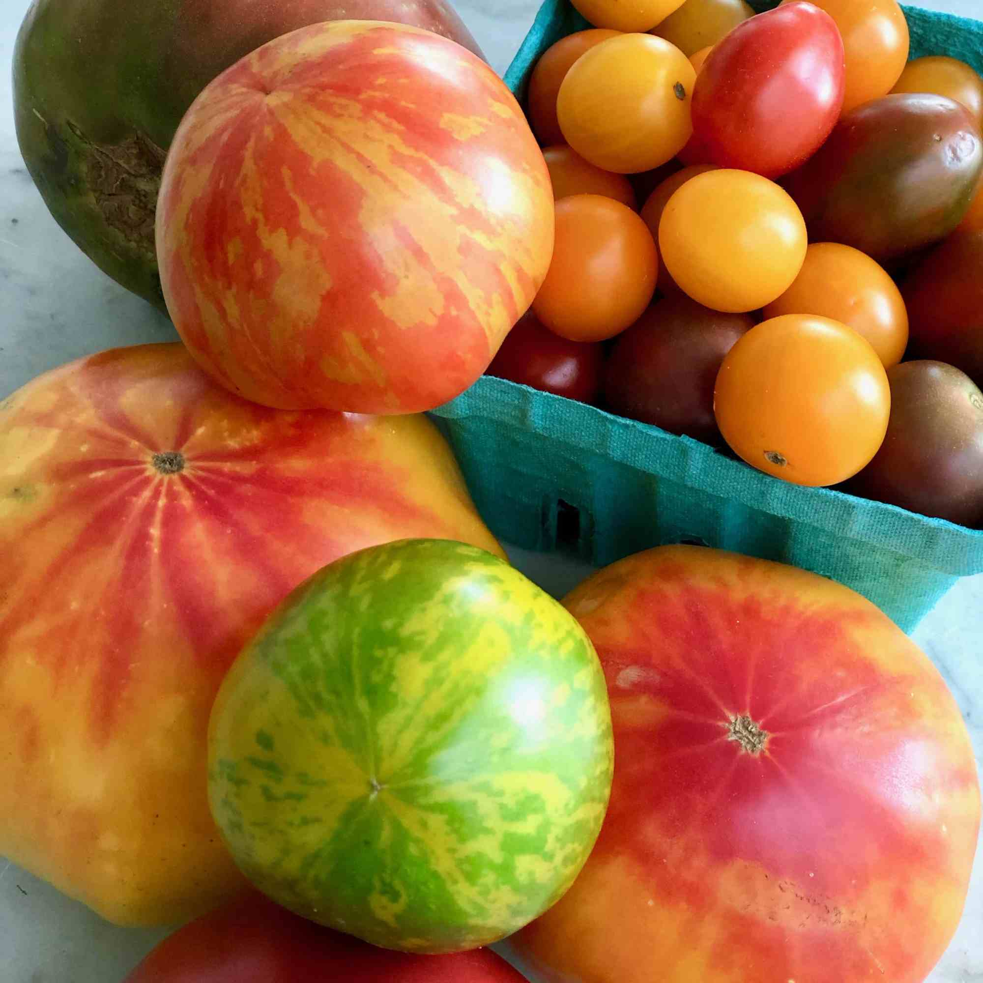 a variety of heirloom tomatoes from the Farmer's Market in a blue box