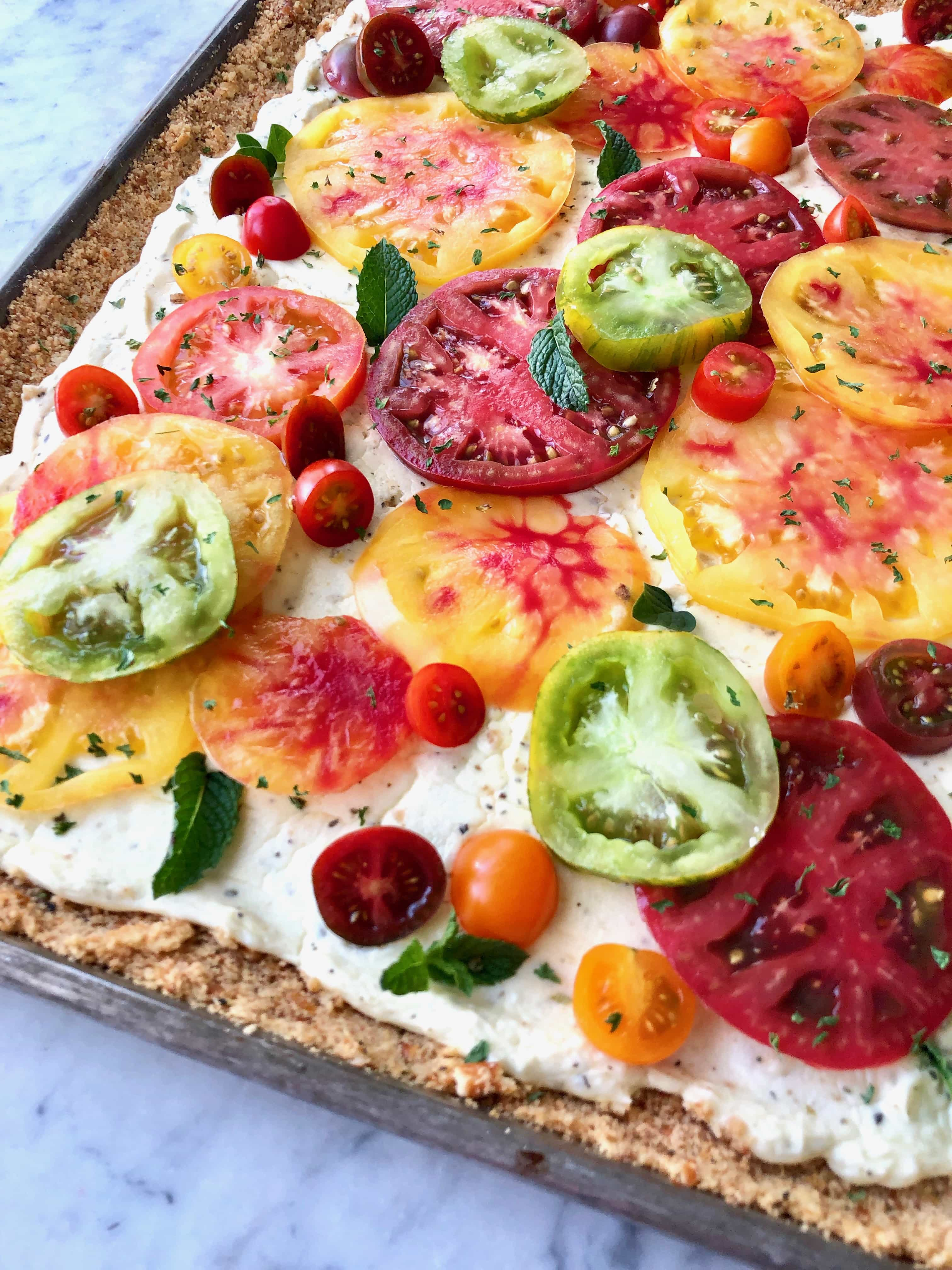 red, green and orange heirloom tomatoes on a tart with pretzel crust and ricotta filling