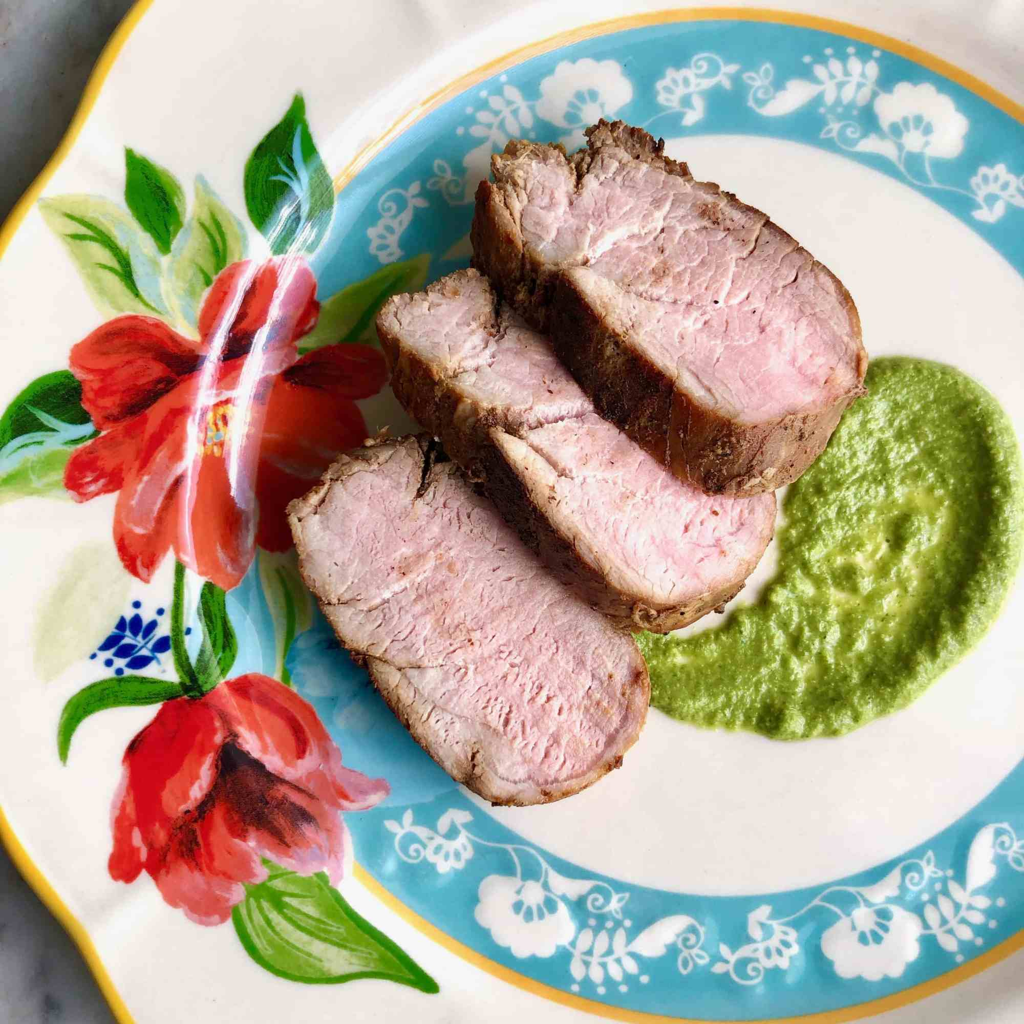 grilled pork tenderloin with chimichurri sauce on a floral plate