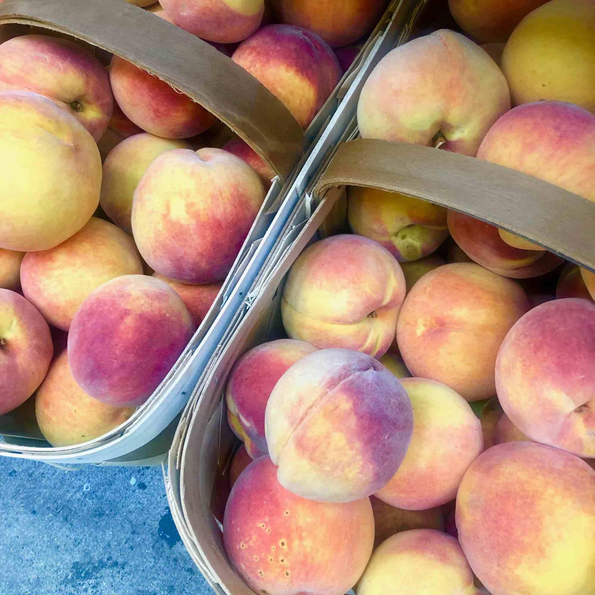 peaches in a basket at farmer's market