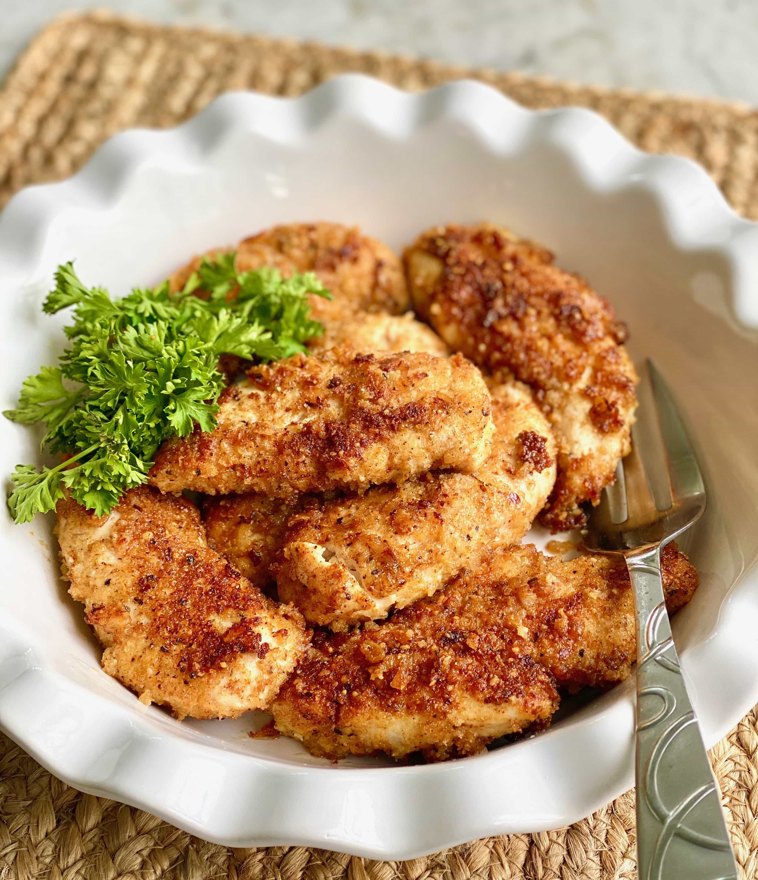 crunchy parmesan chicken in a white bowl with parsley