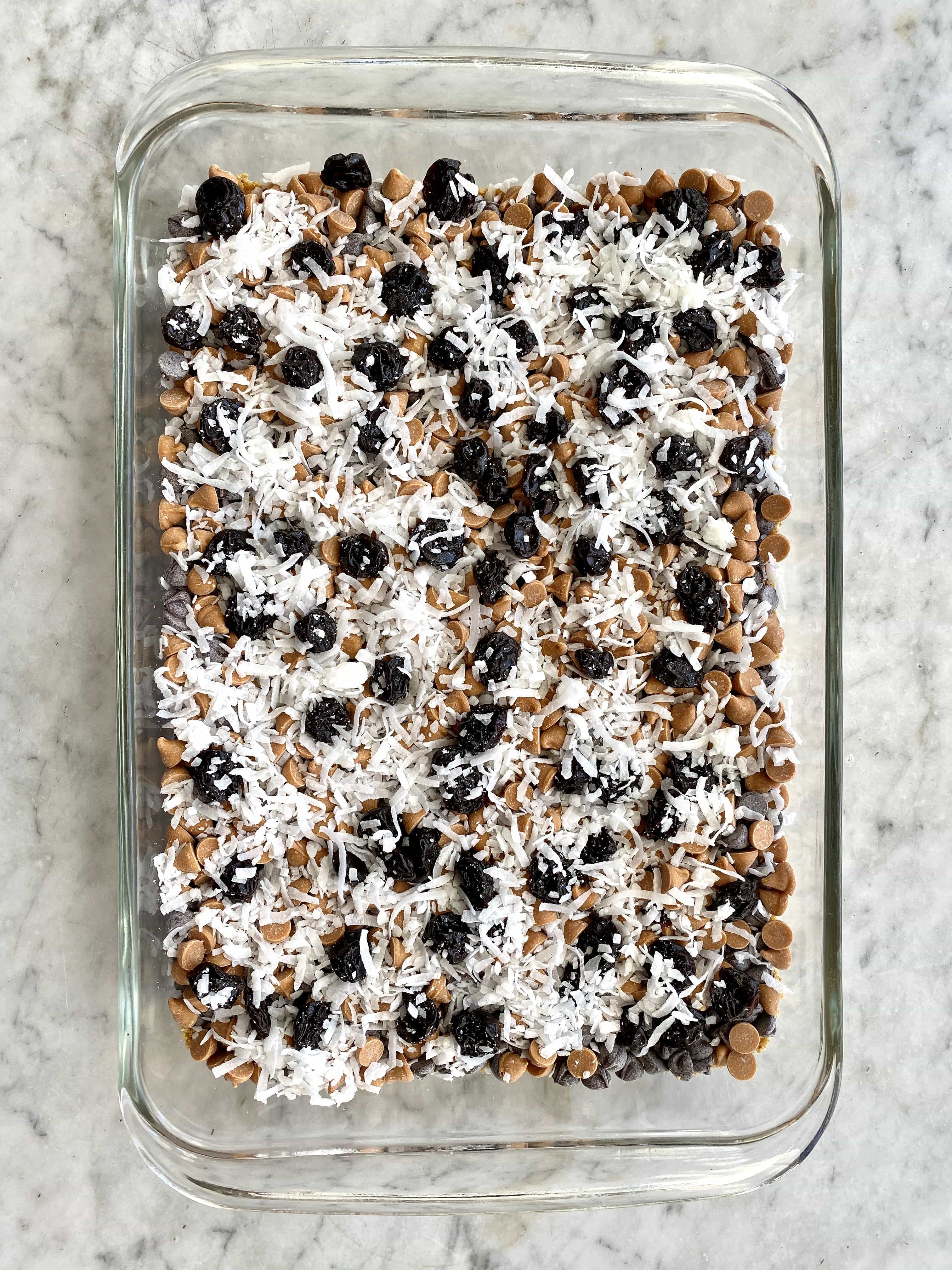cherry magic bars in a glass dish ready to go in oven