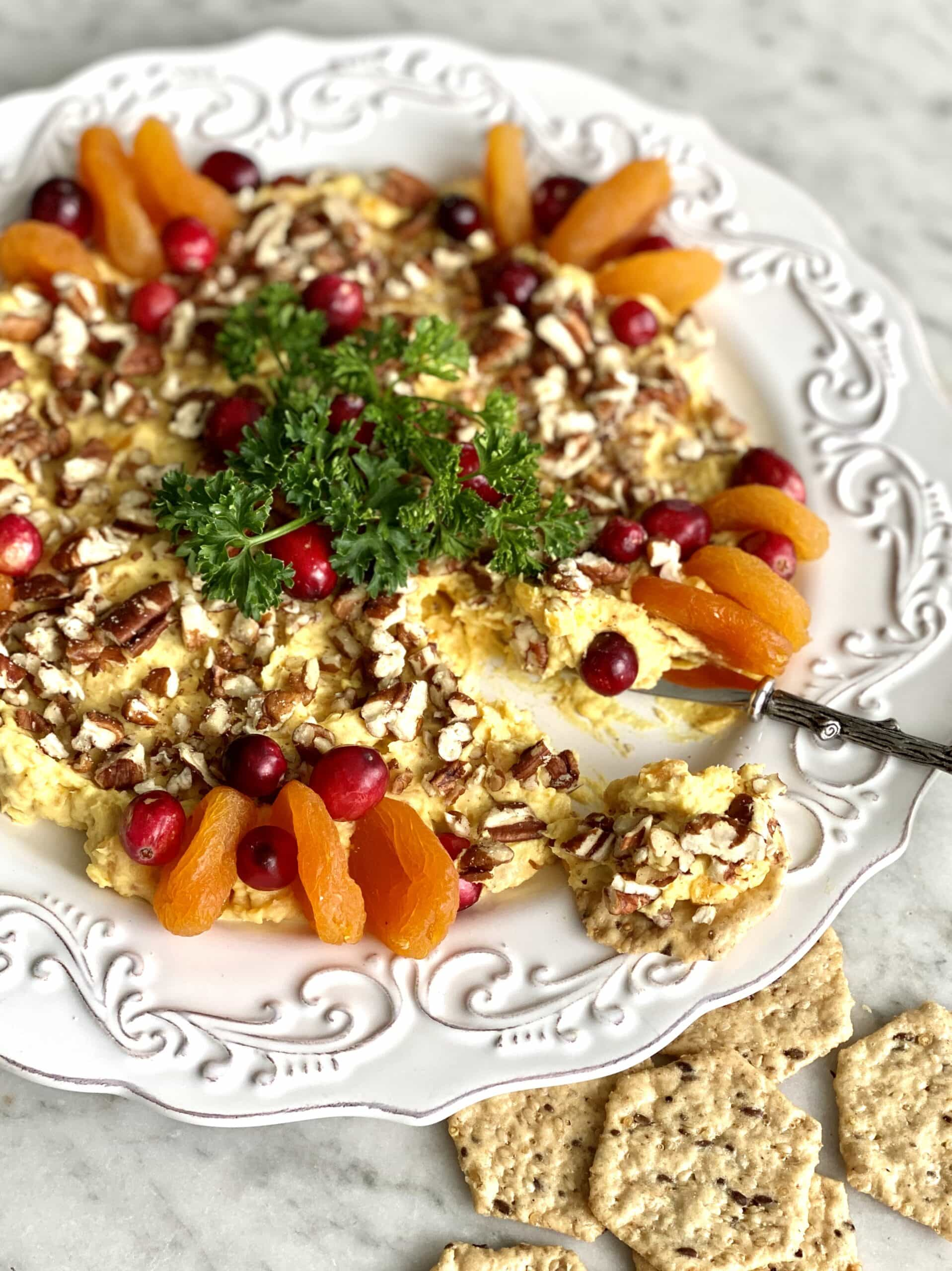 cheese spread on a white plate with crackers, apricots and cranberry garnish