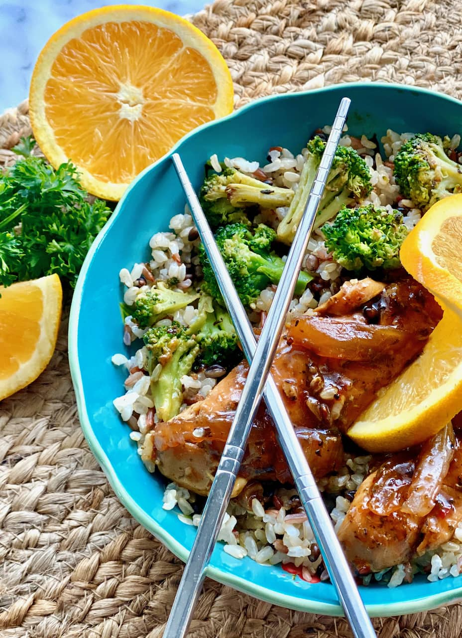 jerk chicken, rice and broccoli in a blue bowl with chopsticks on top