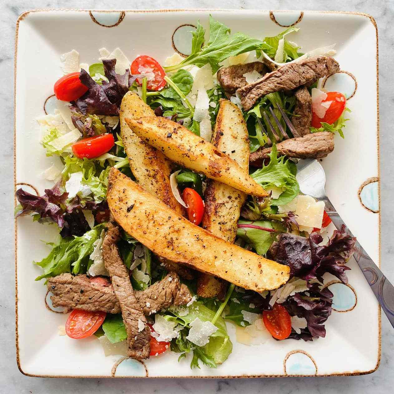 potato and steak salad on a white plate