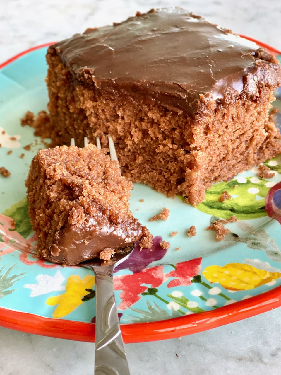 slice of chocolate cake on a blue plate with a bite on a fork