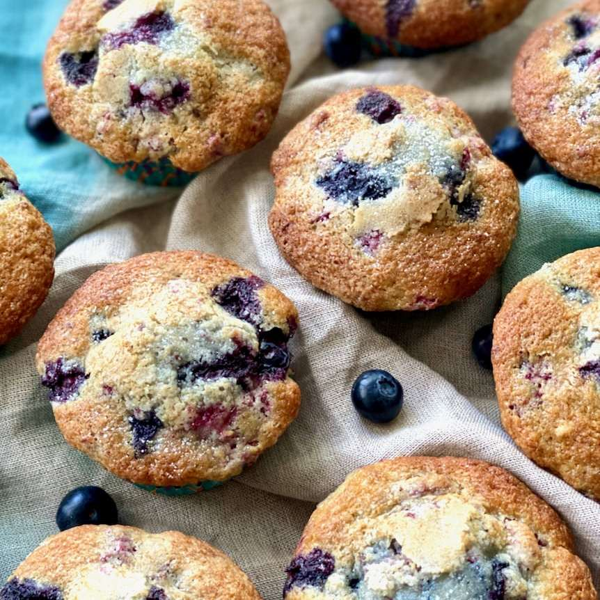 blueberry muffins arranged with blueberries on a blue napkin