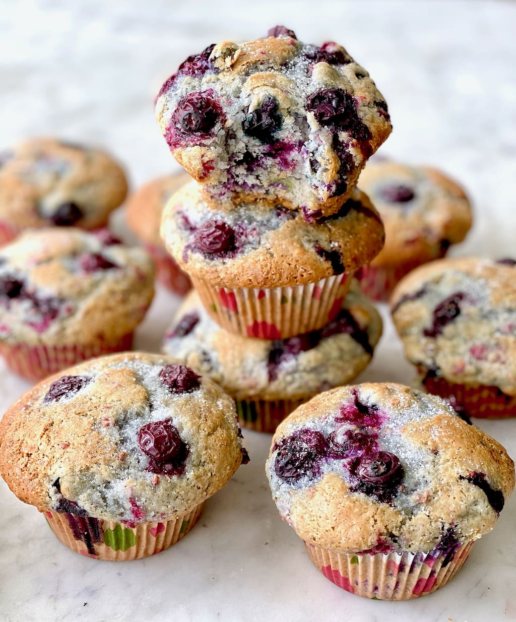 blueberry muffins stacked on top of each other with one opened up to show insides