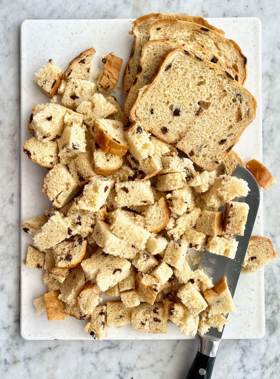 cubed chocolate chip brioche loaf on a white cutting board