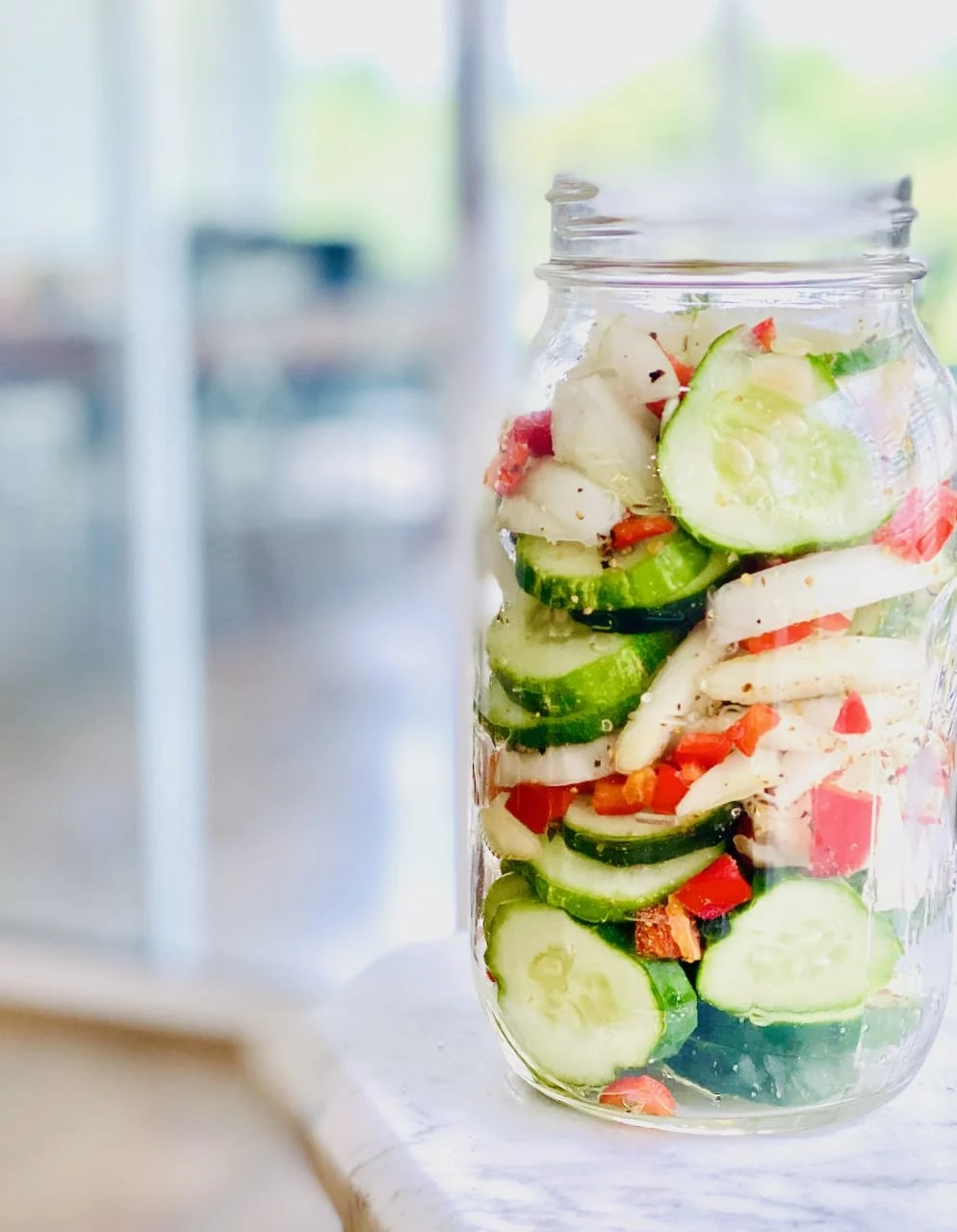 cucumbers, onions and red peppers in a mason jar on a slate table with blurred background