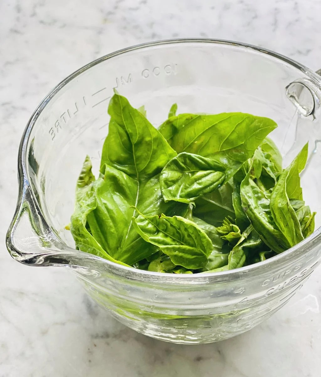 fresh basil leaves in a glass measuring cup