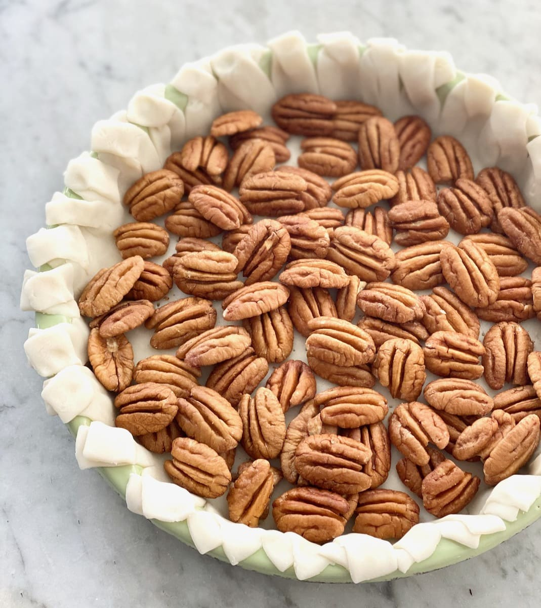 large pecans lining the bottom of a pie crust.