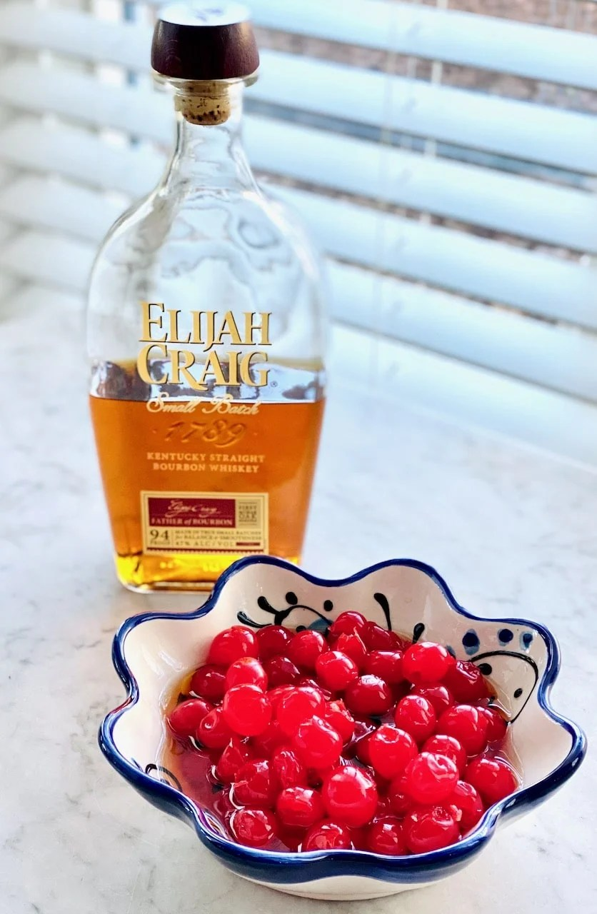 a bottle of bourbon and cherries in a blue bowl.