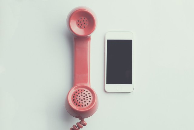 A red corded-phone next to a white smartphone.