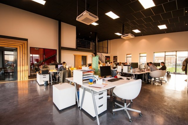A brightly lit office space with numerous desks and people.