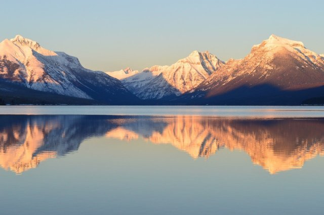 Mountains during a sunrise. You are viewing them from across a glassy lake.